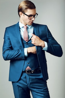 スタジオでポーズをとって青いスーツとおしゃれなメガネの若いエレガントなハンサムな実業家男性モデル