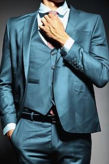 Modello maschio del giovane uomo d'affari bello elegante in un vestito che lega la cravatta