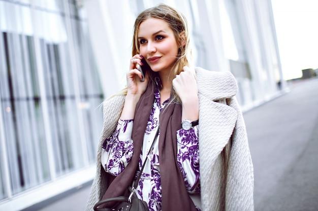 Giovane signora elegante che fa chiamata sul suo smartphone, indossa un cappotto beige alla moda di lusso, sciarpa di cashmere color talpa e abito floreale, in posa vicino al centro business modello.