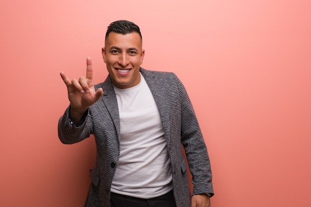 Young elegant latin man doing a rock gesture