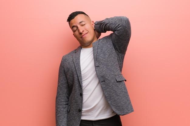 Молодой элегантный латинский мужчина страдает от боли в шее