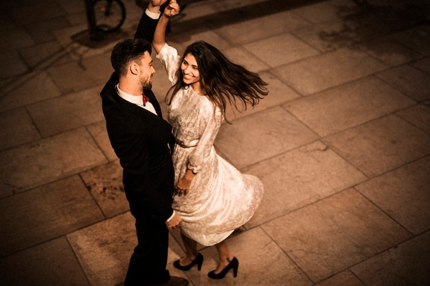 Молодой элегантный мужчина держит руку кружащейся привлекательной жизнерадостной женщины Бесплатные Фотографии