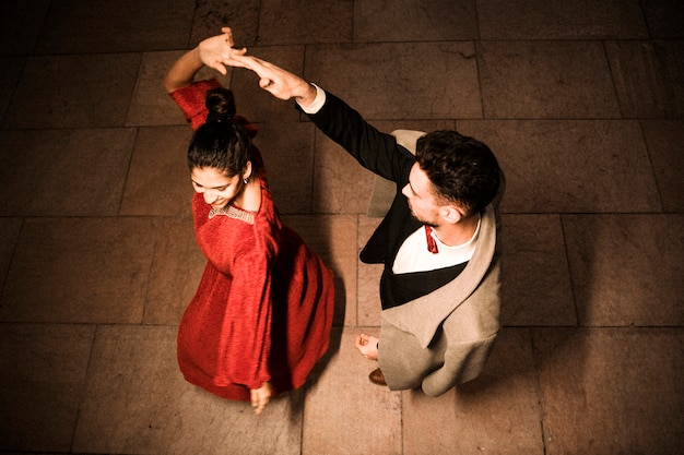 Young elegant man holding hand of whirling charming cheerful woman