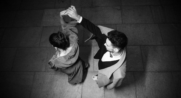 Young elegant man holding hand of whirling charming woman