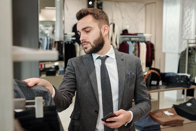 Молодой элегантный мужчина в костюме выбирает новую куртку или рубашку, просматривая новую коллекцию в современном бутике