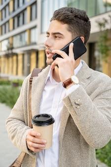 白いシャツとベージュのジャケットを着た若いエレガントな男性が飲み物を飲み、スマートフォンで大規模な現代の建物に対してクライアントや同僚と話している