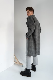 Young elegant man in stylish gray plaid coat in fashionable trousers in leather black trendy boots stands near vintage white wall in studio. modern handsome guy in fashion seasonal outerwear in room.