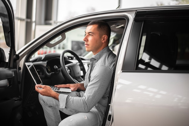 Giovane uomo elegante che prova un'automobile