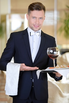 Young elegant man waiter serve wine at restaurant.