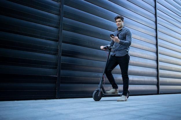 Giovane uomo elegante che cammina con scooter elettrico e utilizzando smart phone
