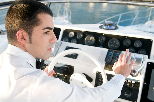 Young elegant man at yacht control in the bay