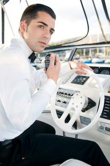 Young elegant man at yatch control