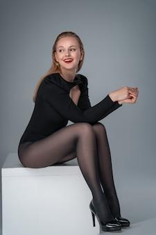 Молодая элегантная модель в боди и колготках улыбается