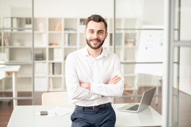 Молодой элегантный офис-менеджер или брокер, скрестив руки на груди, стоя на рабочем месте