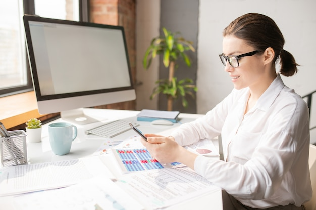 Young elegant office manager scrolling in smartphone while sitting by desk and working with financial documents