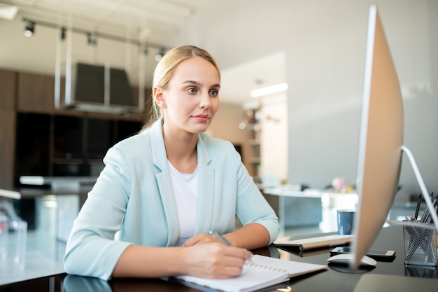 Young elegant office worker looking at computer screen while sitting in front of monitor while making notes