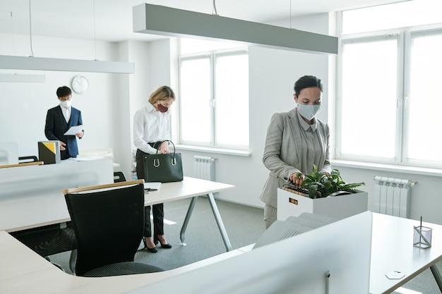 Молодые элегантные офисные работники в формальной одежде и защитных масках стоят у своих столов и собираются начать работу после карантина.