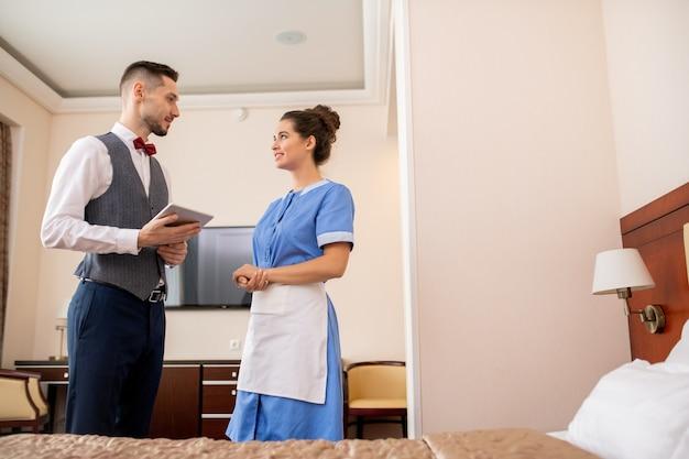 Молодой элегантный портье с тачпадом смотрит на симпатичную горничную в униформе во время разговора в гостиничном номере