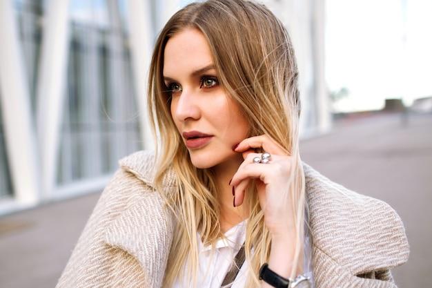 若いエレガントなかなりブロンドの女性が通りでポーズ、自然な官能的な外観、笑顔でカメラを見て、トレンディなベージュのコートと高級アクセサリー、春秋の時間、柔らかな色を着ています。