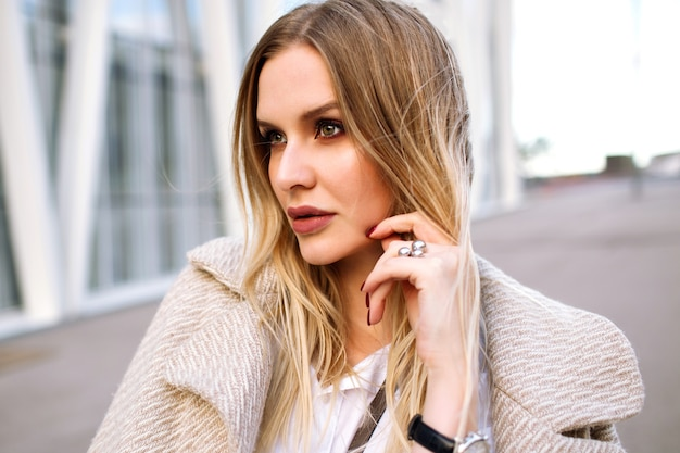 Young elegant pretty blonde woman posing on the street , natural sensual look , smiling and looking on camera , wearing trendy beige coat and luxury accessories, spring autumn time, soft colors.