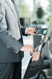 자동차 한 대 옆에 서서 문을 열려고 하는 동안 원격 제어 경보 시스템을 사용하여 정장을 입은 젊고 우아한 새 차 판매자
