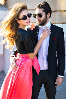 若いエレガントなセクシーなカップルが路上で抱擁し、スーツと魅力的なイブニングドレスを着て、ヨーロッパでの新婚旅行の休暇、豪華なスタイル、愛、スタイリッシュな恋人たちを楽しんでください