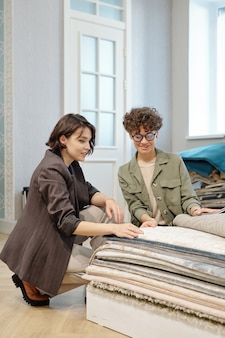 Young elegant shop assistant consulting client while choosing sample of new carpet or floor coverings in contemporary studio of interior design