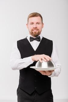 Молодой элегантный официант в черном жилете и галстуке-бабочке держит колпак с едой, стоя перед камерой в изоляции