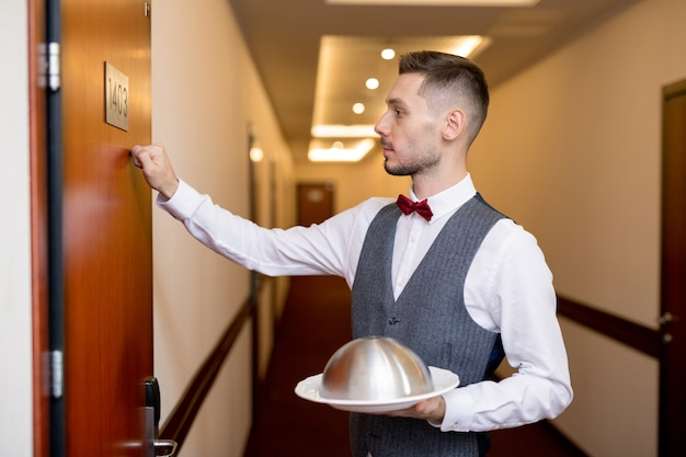ゲストの1人のクローシュに食べ物を押しながらホテルの部屋の木製のドアをノックして若いエレガントなウェイター