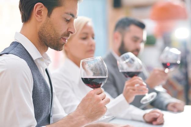 Молодой элегантный эксперт винодельни или винодел смотрит на красное вино в бокале, оценивая его цвет и запах
