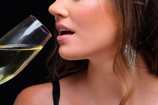 Of young elegant woman drinking champagne against black