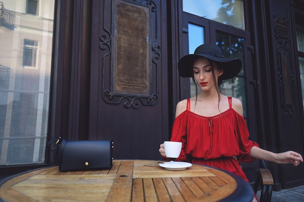 Молодая элегантная женщина в красном платье и винтажной шляпе с чашкой кофе сидит в кафе