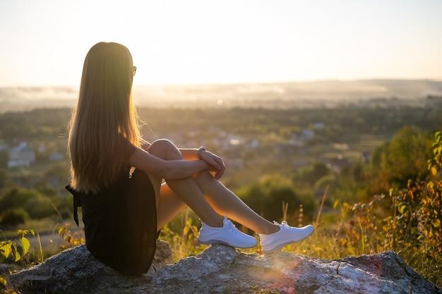 Молодая элегантная женщина в черном коротком платье и белых кроссовках сидит на скале, расслабляясь на открытом воздухе в летний вечер. модная дама, наслаждаясь теплым закатом на природе.