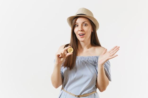 파란 드레스를 입은 젊고 우아한 여성, 흰색 배경에 격리된 황금색 비트코인 동전을 들고 긴 머리를 한 모자. 사람들의 라이프 스타일 온라인 가상 통화 개념입니다. 광고 영역입니다. 복사 공간