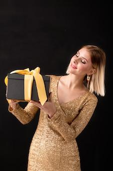 노란색 리본으로 묶인 검은 giftbox를보고 황금 드레스에 젊은 우아한 여자가 안에 생일 선물이 무엇인지 추측하는 동안