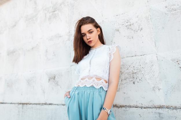 세련 된 파란색 바지에 세련 된 레이스 탑에 젊은 우아한 여자 모델은 흰색 빈티지 벽 근처 도시에 서 있습니다. 거리에서 매력적인 패션 모델 소녀입니다. 여름 스타일.