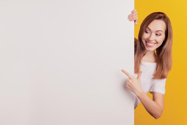 빈 공간 흰색 빌보드 포스터를 가리키는 젊은 우아한 여자