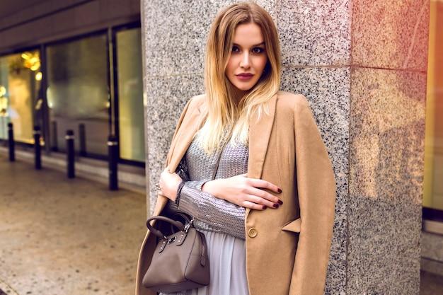 ショッピングセンターの近くの通りでポーズをとる若いエレガントな女性、魅力的な流行の衣装、ベージュのコート、銀のセーターとドレス、春、自然の美しさ