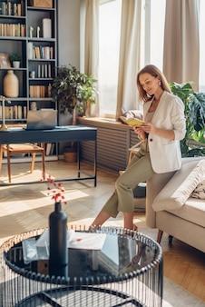 家で本を読んでいる若いエレガントな女性。