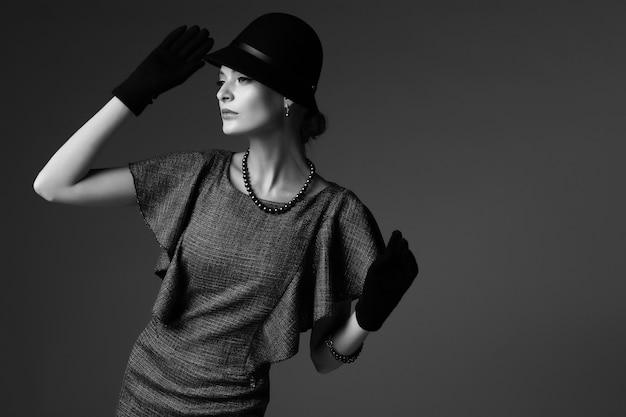 젊은 우아한 여자, 복고풍 패션, 모자, 장갑, 드레스. 흑백 이미지.