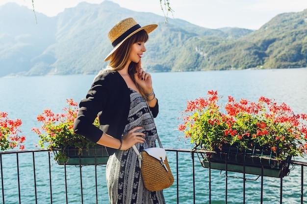 Giovane donna elegante con cappello di paglia in un balcone con fiori sul lago di como