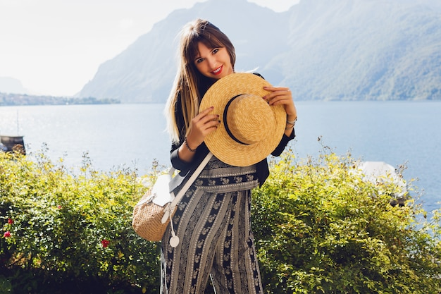 Giovane donna elegante con cappello di paglia nel lago di como