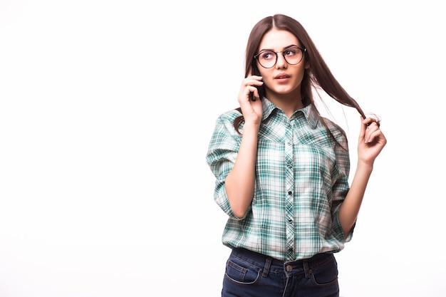 Giovane donna elegante che parla sul telefono cellulare contro il bianco