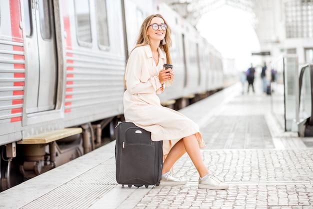 Молодая элегантная женщина ждет с багажом отправления поезда на вокзале
