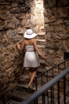 Молодая элегантная женщина в большой шляпе изучает древний каменный замок