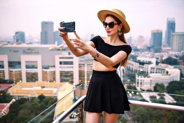 Young elegant woman wearing fashionable trendy summer outfit making touristic selfie at terrace of luxury hotel