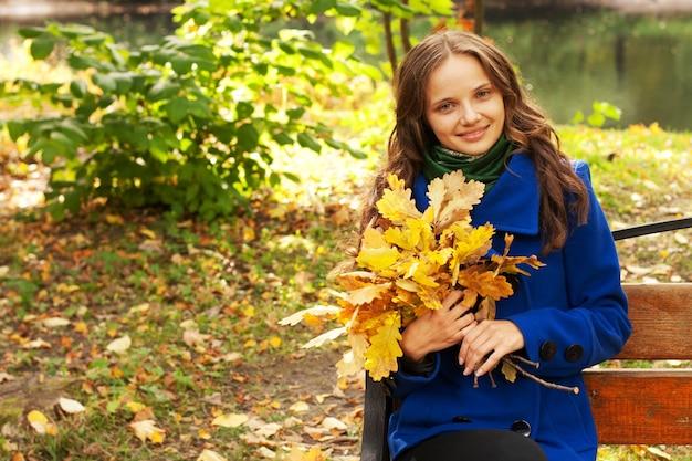 ベンチに座って紅葉を持つエレガントな女