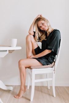 巻き毛の若いエレガントな女性は、白いアパートでモーニンコーヒーと黒のガウンを着ています。彼女はカメラに微笑んでいます。明るい部屋で目覚めるリラックスした美しい女性。