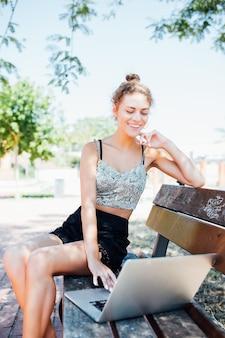 Giovane donna elegante con cappello in abito bianco seduto su una panchina nel parco e lavorando al computer portatile