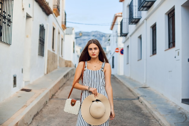 Young elegant woman with straw hat walking on the narrow streets of the old town.